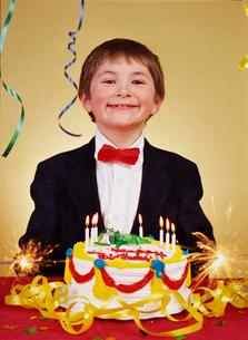 Boy smiling beside his birthday cakeの写真素材 [FYI01990565]