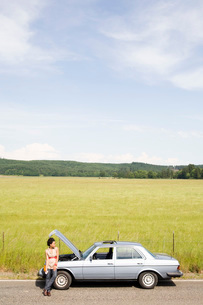 Woman waiting next to broken down carの写真素材 [FYI01990581]