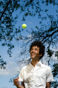 Man tossing tennis ball in the airの写真素材 [FYI01990621]