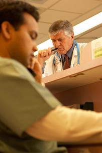 Two men at hospital reception deskの写真素材 [FYI01990654]