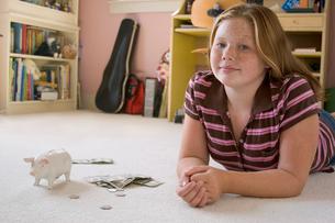 Girl on floor with piggy bank and moneyの写真素材 [FYI01990678]