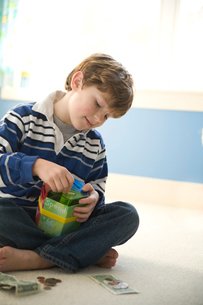 Boy putting money in coin bankの写真素材 [FYI01990729]