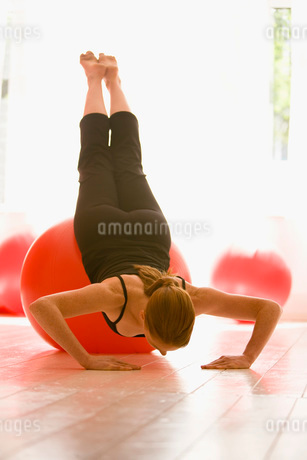 Young woman stretching on exercise ballの写真素材 [FYI01990790]