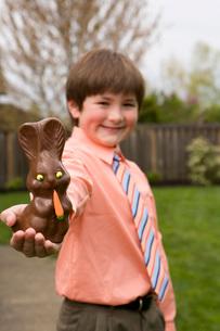 Boy holding chocolate Easter bunnyの写真素材 [FYI01990806]