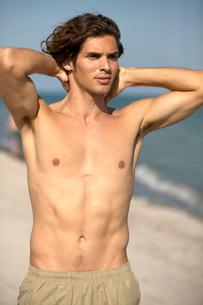 Young Hispanic man stretching on beachの写真素材 [FYI01990832]
