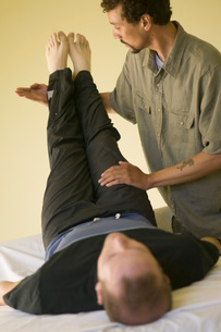 Masseuse stretching out clientの写真素材 [FYI01990885]