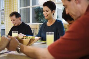 Family saying prayer at dinner tableの写真素材 [FYI01990919]