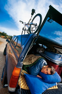 Young man sleeping in back of truckの写真素材 [FYI01990927]