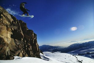 Snowboarder jumping off rock faceの写真素材 [FYI01990939]