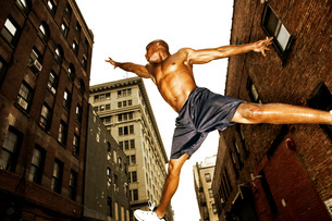 African man jumping in cityの写真素材 [FYI01990944]