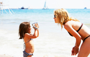 Girl videotaping her mother at beachの写真素材 [FYI01990969]