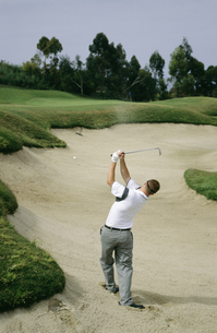 Man playing golf out of sand trapの写真素材 [FYI01990999]