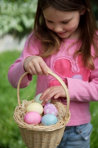 Girl holding Easter eggs in a basketの写真素材 [FYI01991055]