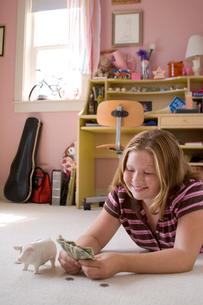 Girl on floor with her piggy bankの写真素材 [FYI01991058]