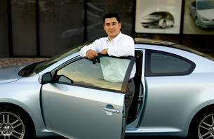 Hispanic man with new carの写真素材 [FYI01991059]