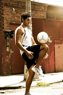 Hispanic man kneeing soccer ballの写真素材 [FYI01991106]