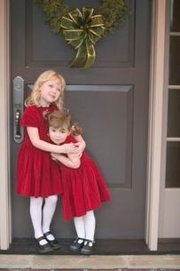 Young girls hugging by Christmas wreathの写真素材 [FYI01991203]