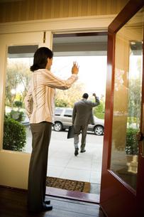 Woman waving to husband by open doorの写真素材 [FYI01991208]