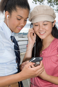 Two girls with mp.3 player outdoorsの写真素材 [FYI01991237]