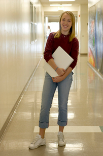 girl in school hallway holding laptopの写真素材 [FYI01991320]