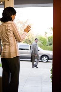 Woman waving to husband by open doorの写真素材 [FYI01991340]