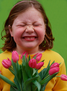 Young girl wrinkling her nose at tulipsの写真素材 [FYI01991384]