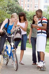 teenagers using hand held devicesの写真素材 [FYI01991391]