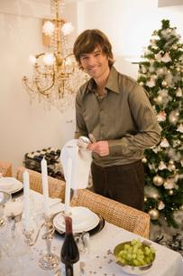 Man setting ornate dinner tableの写真素材 [FYI01991409]