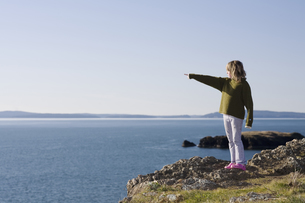 Girl pointing to ocean along cliffの写真素材 [FYI01991428]