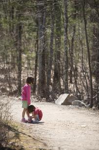 Children tying shoes on gravel roadの写真素材 [FYI01991506]
