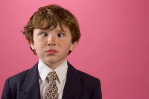 Young boy making a face in business suitの写真素材 [FYI01991541]