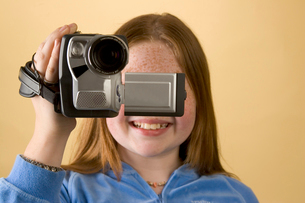 Young girl holding video cameraの写真素材 [FYI01991544]