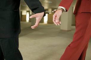 Businesspeople handcuffed togetherの写真素材 [FYI01991576]