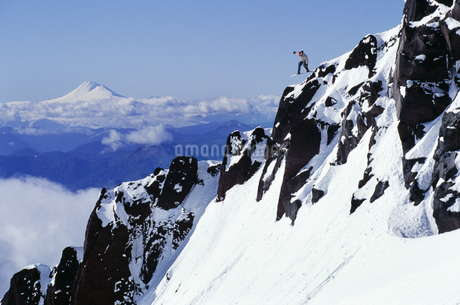 Snowboarder jumping off rock faceの写真素材 [FYI01991628]