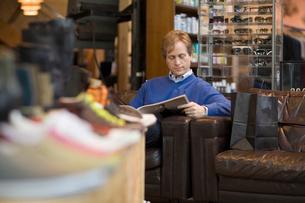 Man reading magazine in clothing storeの写真素材 [FYI01991631]