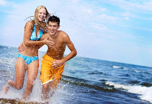 Couple running in waves at beachの写真素材 [FYI01991689]