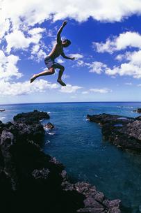 Man jumping off cliff into oceanの写真素材 [FYI01991705]