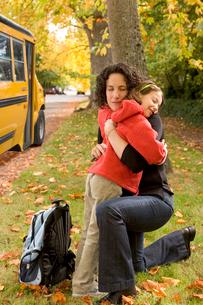 Mother hugging daughter by school busの写真素材 [FYI01991782]