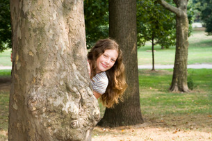 Girl peeking out from behind treeの写真素材 [FYI01991820]