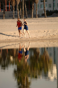 African couple running on beachの写真素材 [FYI01991825]