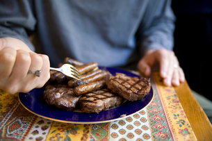 Man holding fork over plate of meatの写真素材 [FYI01991828]