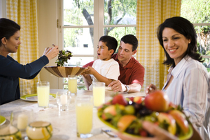 Family passing food at dinner tableの写真素材 [FYI01991834]