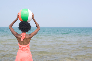 Woman holding a beach ball in waterの写真素材 [FYI01991840]