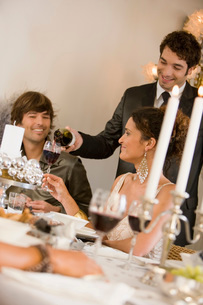 Man pouring wine at dinner partyの写真素材 [FYI01991881]