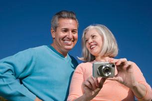Couple looking at digital cameraの写真素材 [FYI01991920]