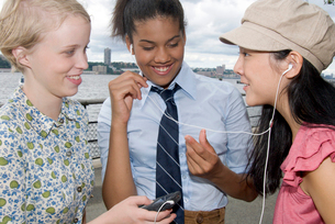 Three girls with mp.3 player outdoorsの写真素材 [FYI01991925]