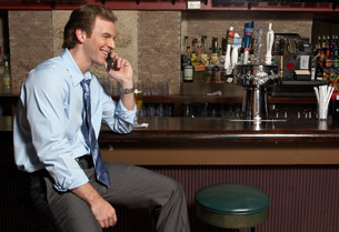 Businessman talking on cell phone at barの写真素材 [FYI01991936]
