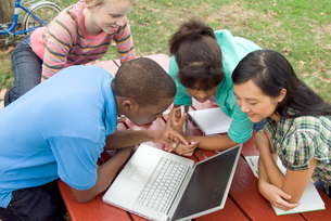 teenagers looking at laptop outdoorsの写真素材 [FYI01992077]