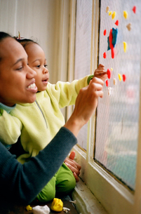 Mother and baby putting clay on windowの写真素材 [FYI01992078]