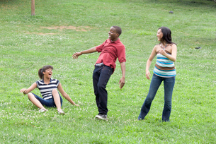 Three teenagers laughing outdoorsの写真素材 [FYI01992088]